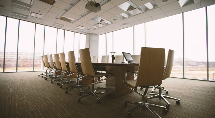 a boardroom table and chairs in the middle of a large meeting room
