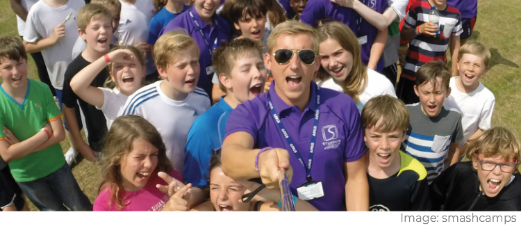 Smash Camps employee taking a selfie surrounded by children