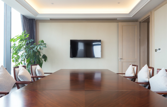 An image of an empty meeting room, with a large wooden table, chairs either side and a flat screen television on the wall.