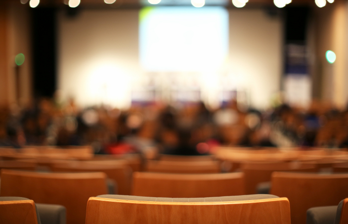 An out-of-focus image of an auditorium with empty seats.